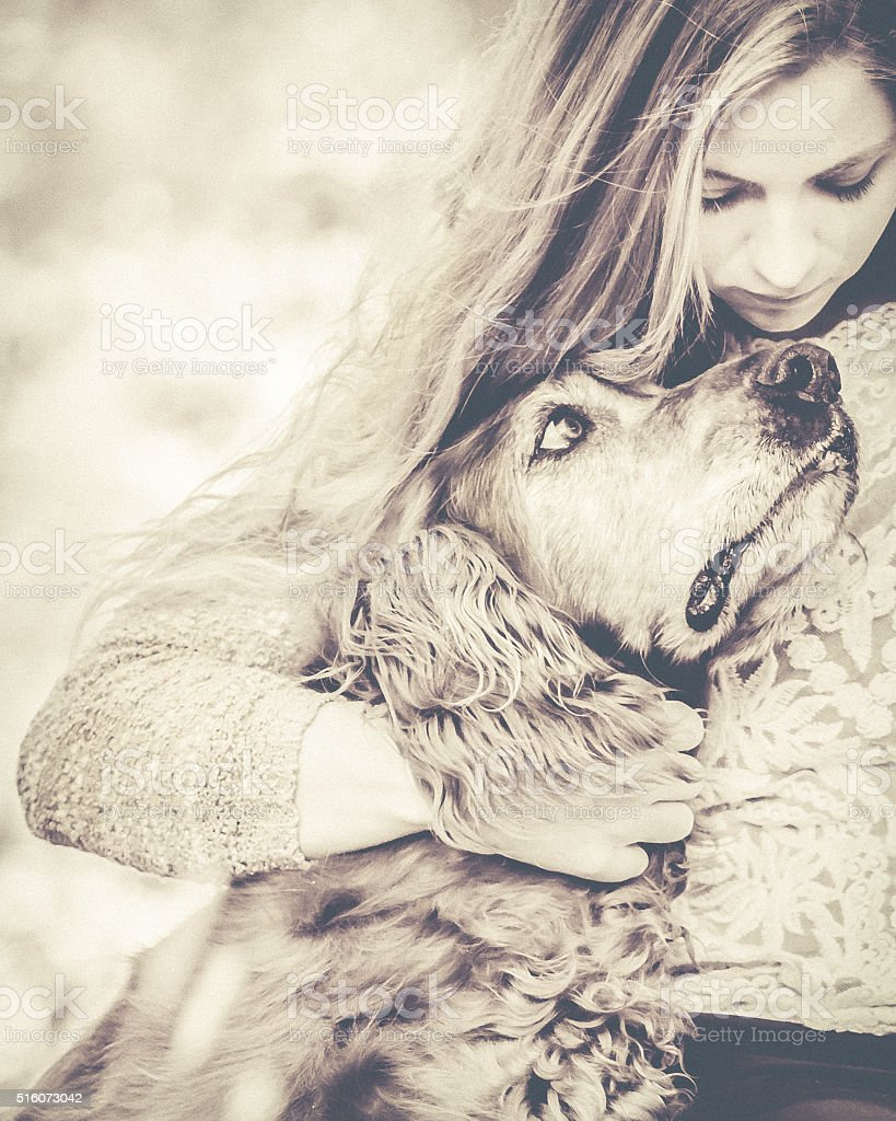 Dog Lover - Woman Hugging Pet Dog - Sepia stock photo