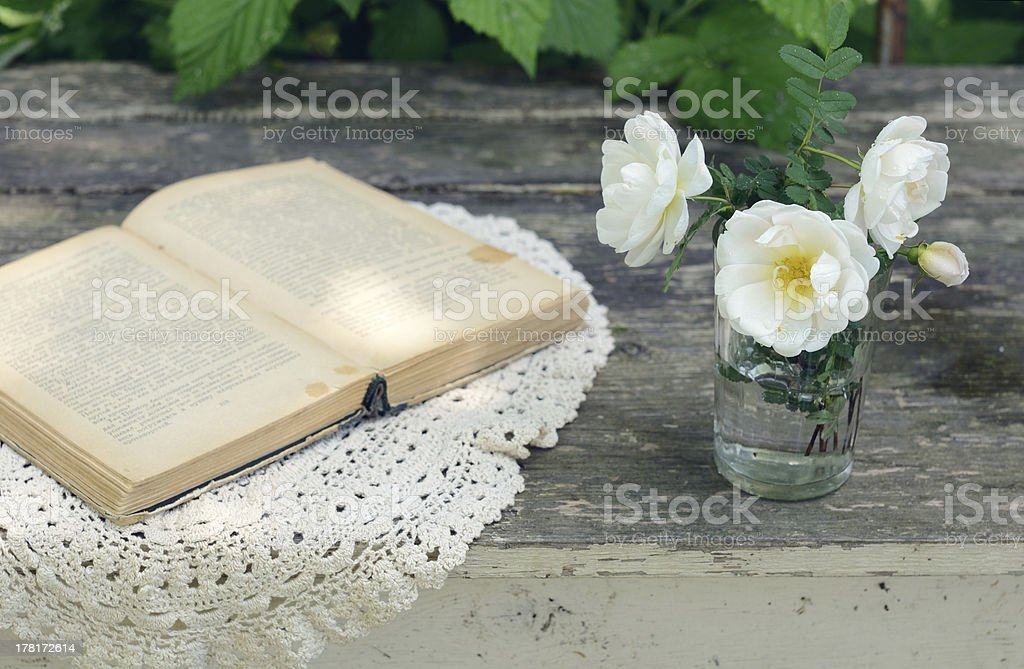Dog rose flowers in a glass on rusted wooden table royalty-free stock photo