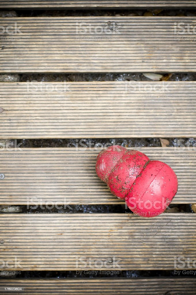 Dog toy Kong covered in dirt saliva on wooden decking stock photo