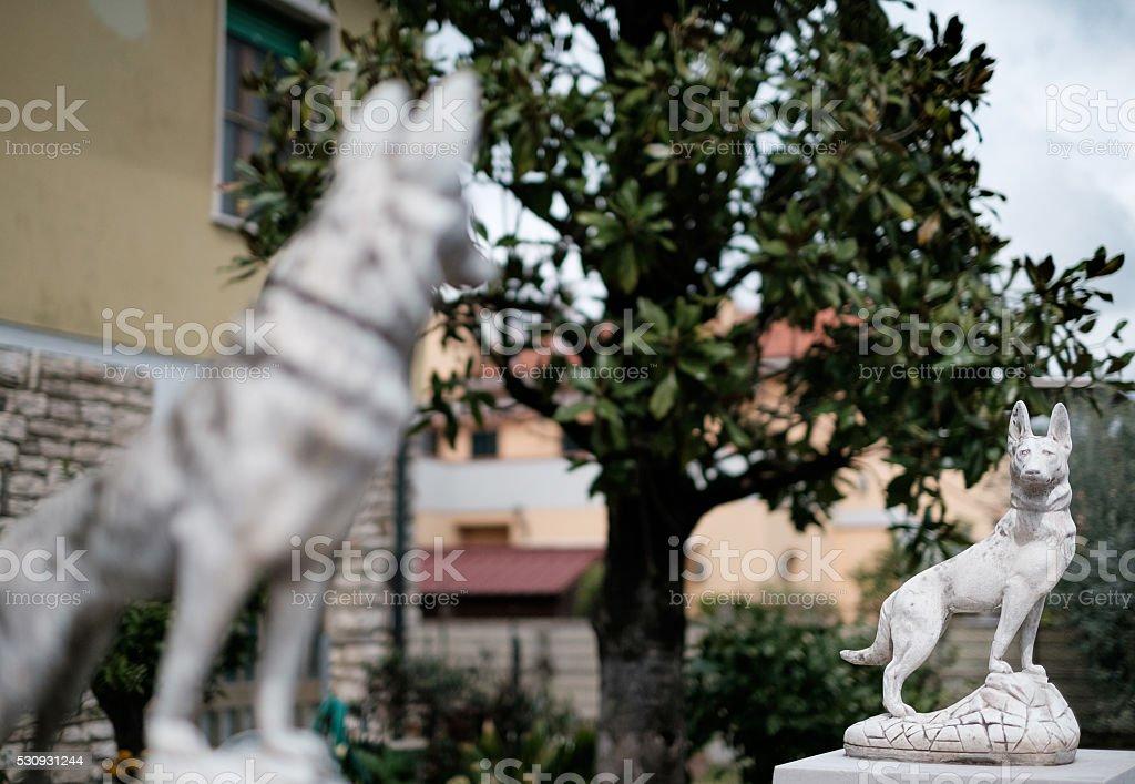 Dog-shaped stone fence post stock photo