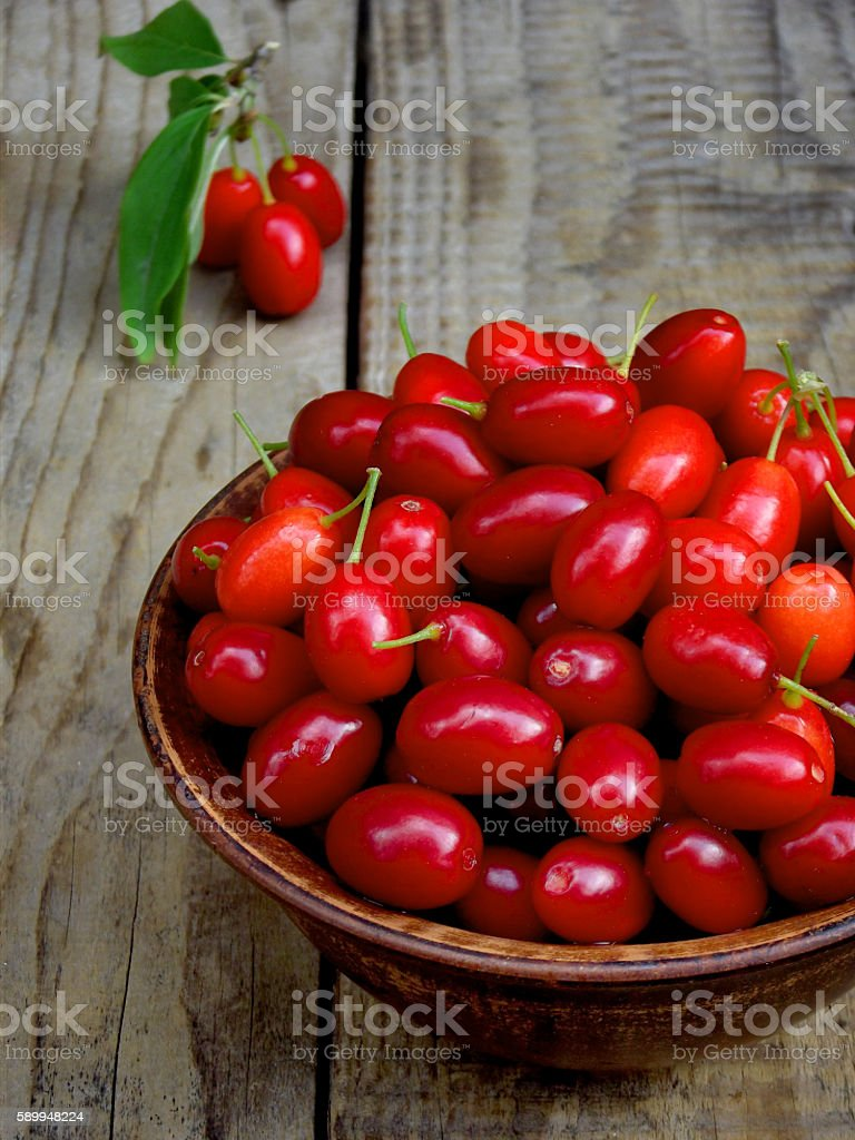 dogwood (cornelian cherry berry) in bowl on wooden background. stock photo