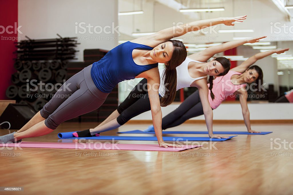 Doing a side plank for yoga class stock photo