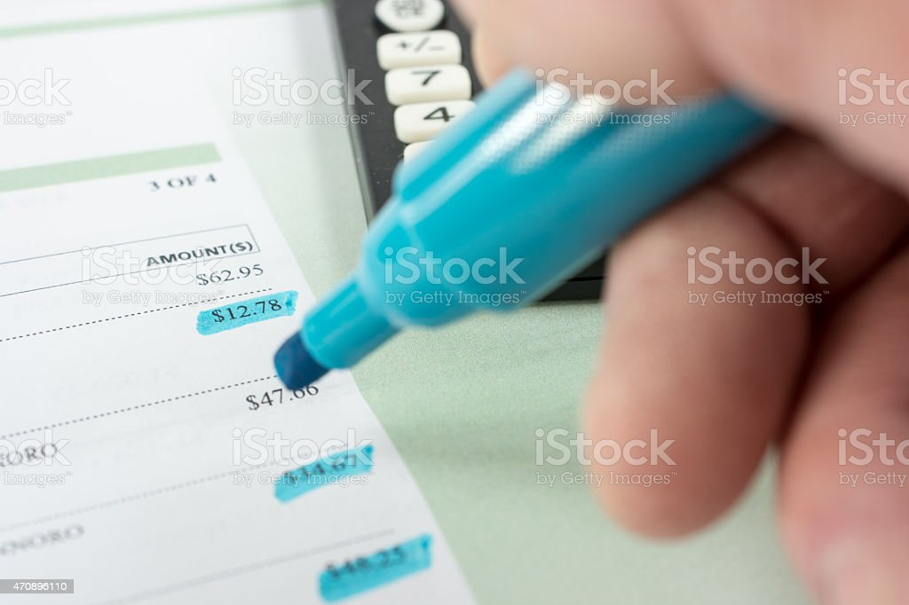 Doing credit card balance  with calculator and highlighting pen stock photo