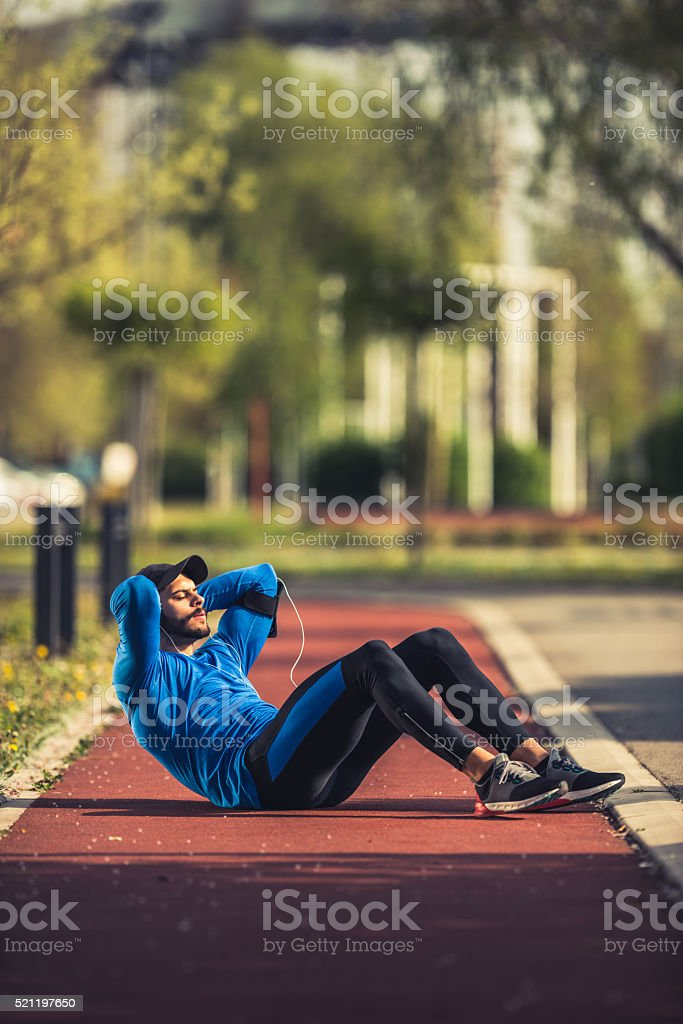 Doing crunches outdoors stock photo