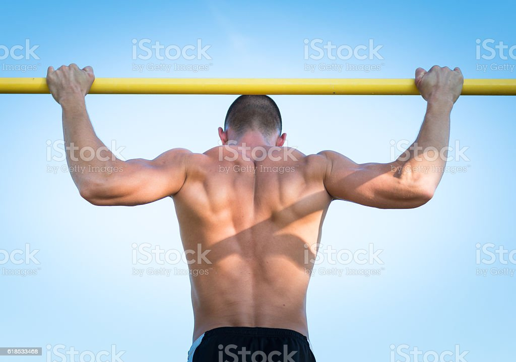 Doing pull-up on horizontal bar stock photo