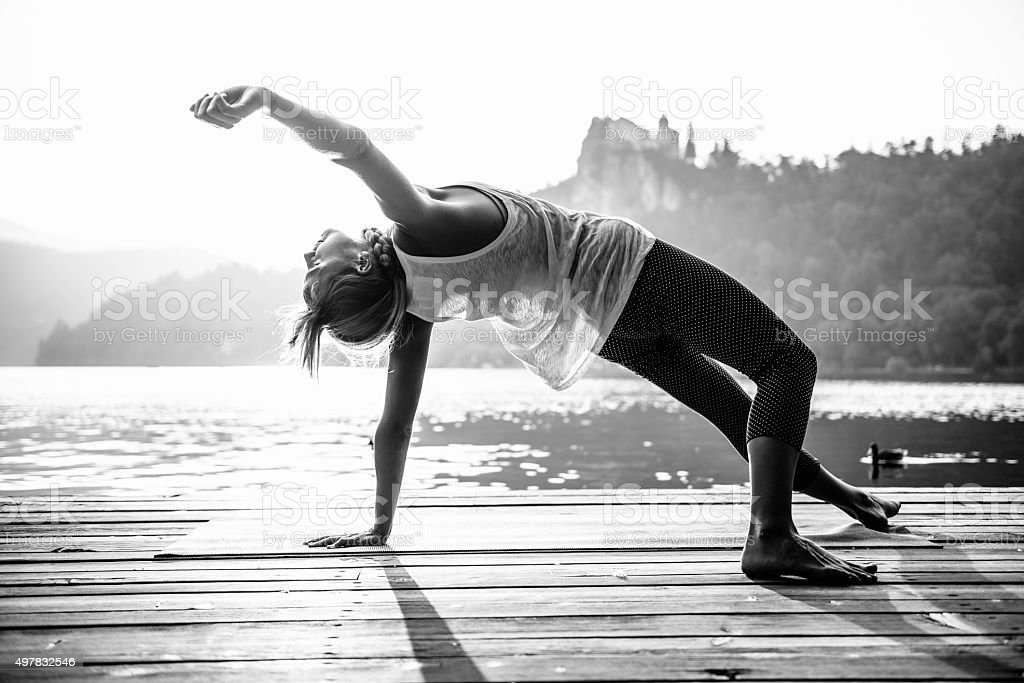 Doing yoga by the lake stock photo
