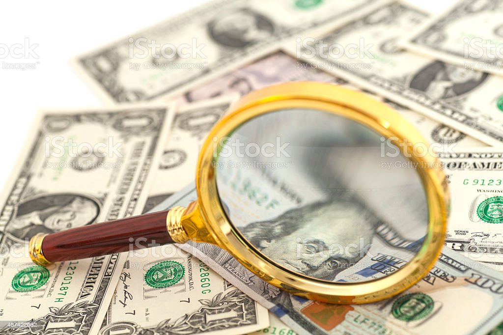 dollar banknotes under magnifying glass isolated stock photo