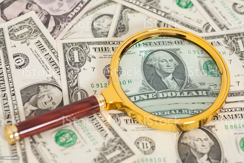dollar banknotes under magnifying glass stock photo