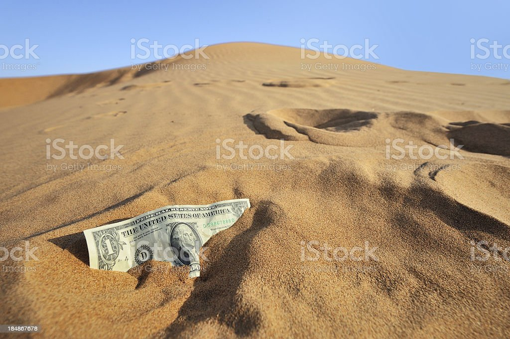 dollar bill in sliding sand stock photo