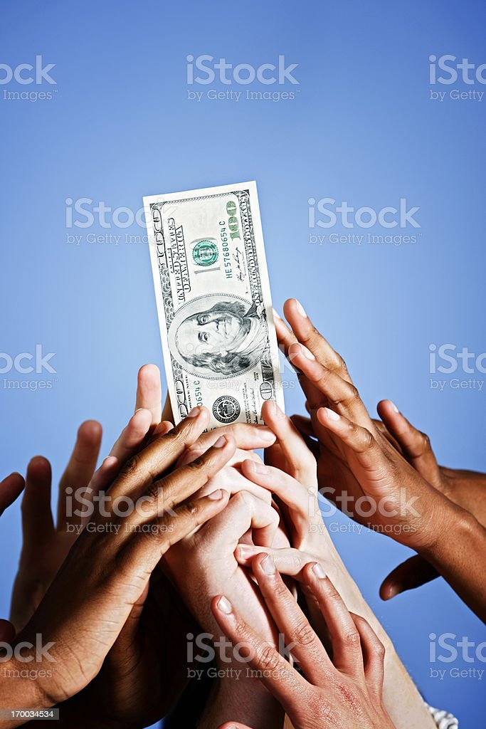 $100 dollar bill literally up for grabs: spotlit against blue stock photo