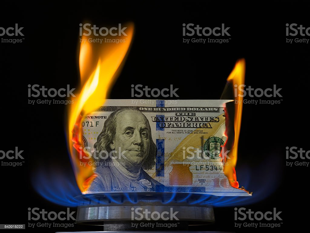Dollar bill on fire in gas burner flame. stock photo