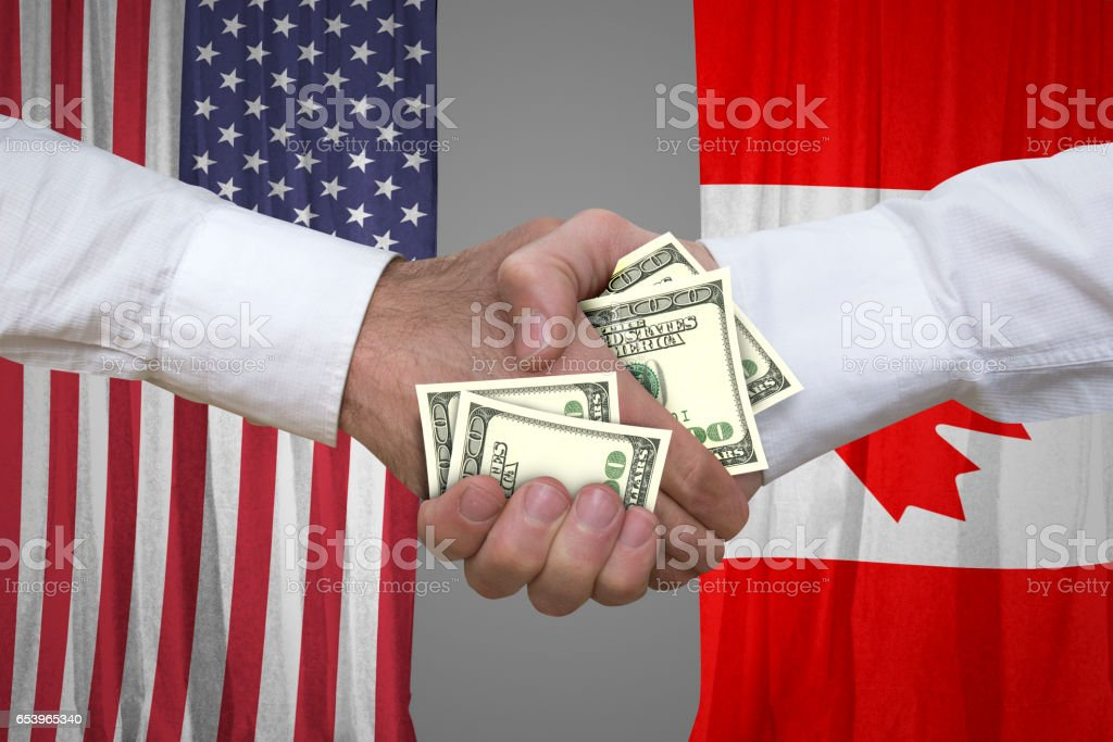 100 dollar bills handshake with USA and Canadian flags background. stock photo