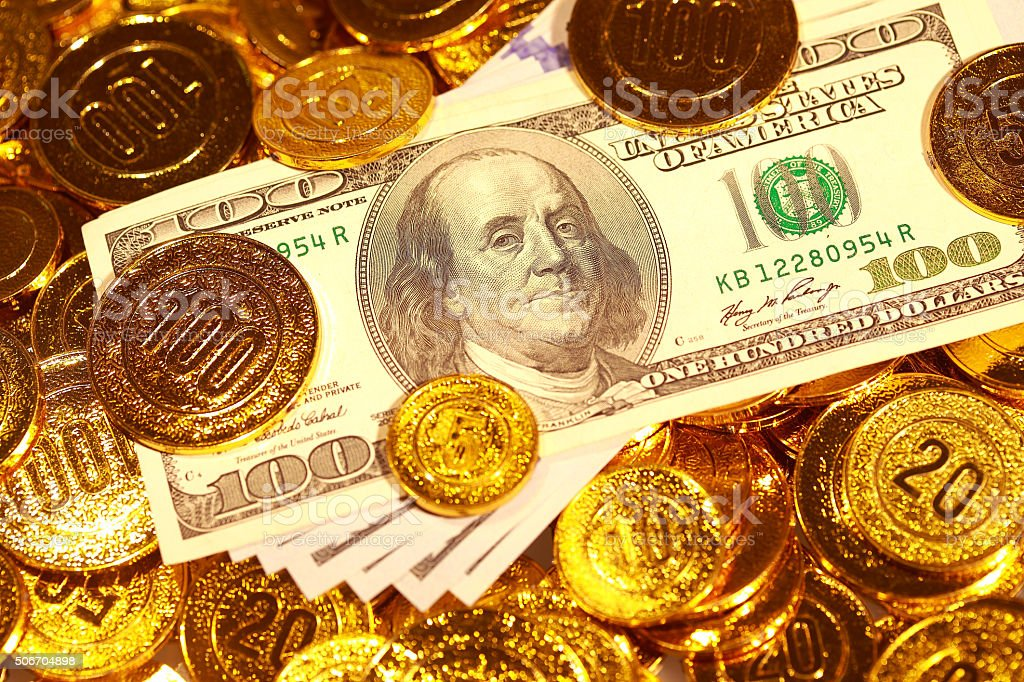 Dollar bills in Golden coins heap stock photo