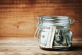 Dollar bills in jar on rustic table. Saving money concept.