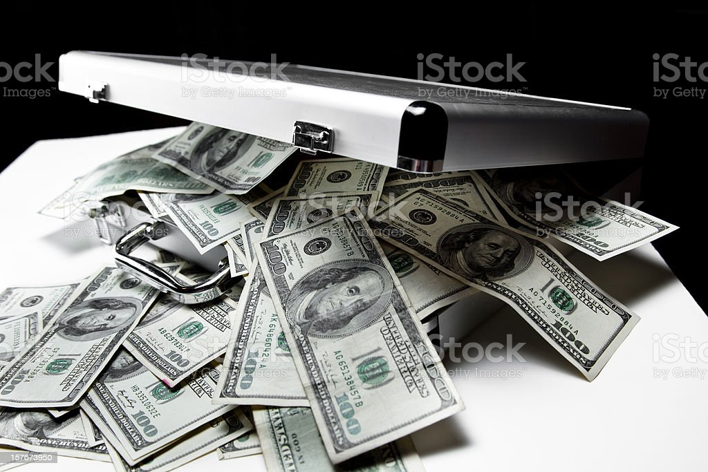 $100 dollar bills spilling out of suitcase. stock photo