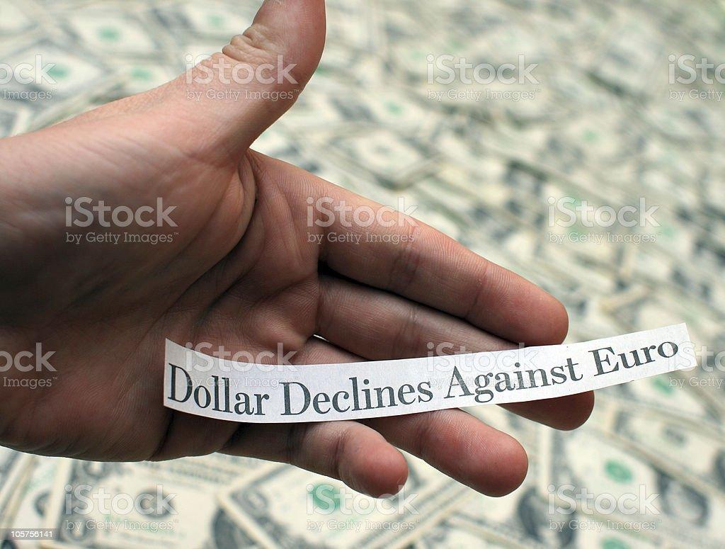 'Dollar Declines Against Euro' - Hand Holding Newspaper Headline stock photo