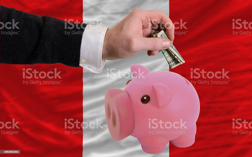 dollar into piggy coin bank and flag of peru stock photo