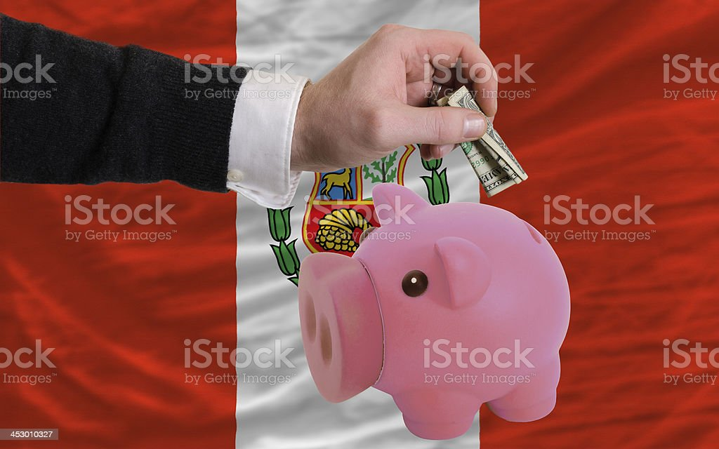dollar into piggy rich bank and  national flag of peru stock photo