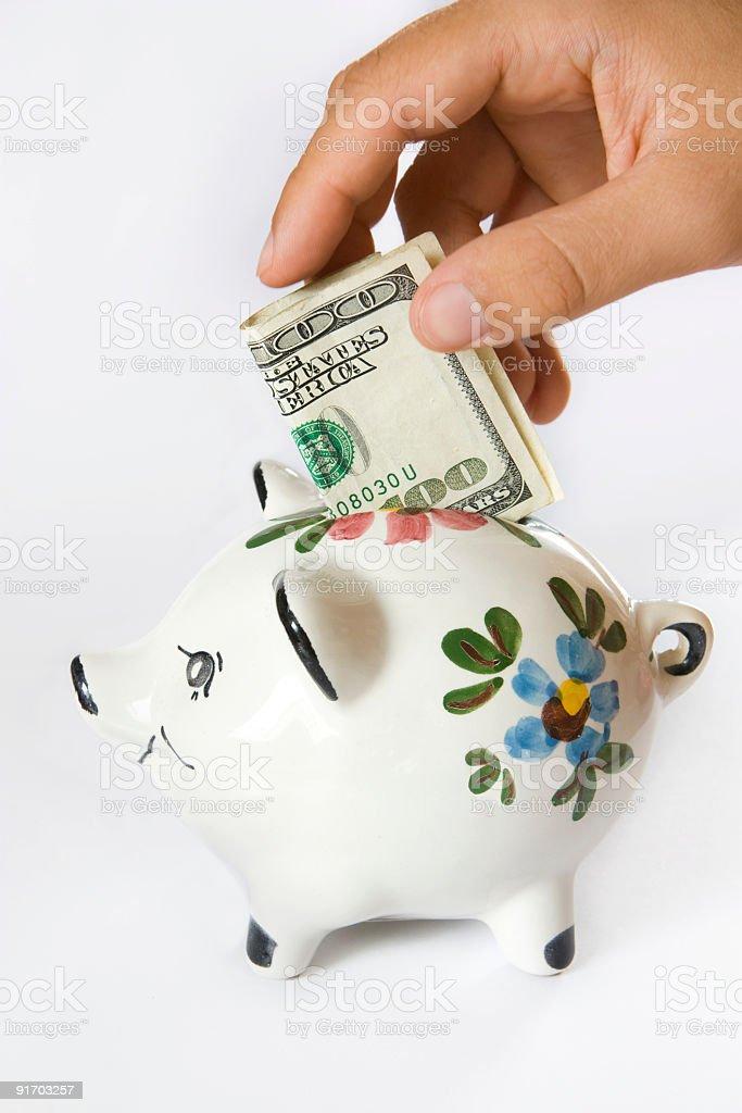 Dollar into Piggybank stock photo