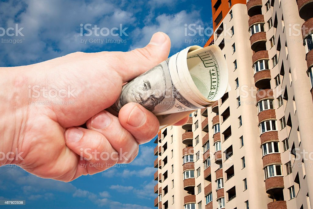 US dollar notes in a hand against  inhabited high-floor house stock photo