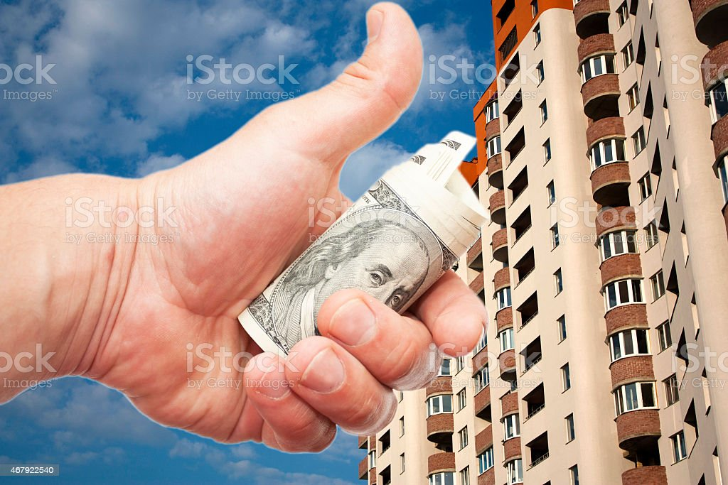US dollar notes in a hand against  the inhabited  hous stock photo