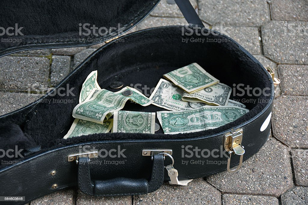 dollar tips in guitar case stock photo
