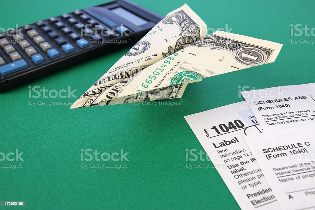 Dollar-Bill Paper Airplane Next to Tax Forms and Calculator stock photo