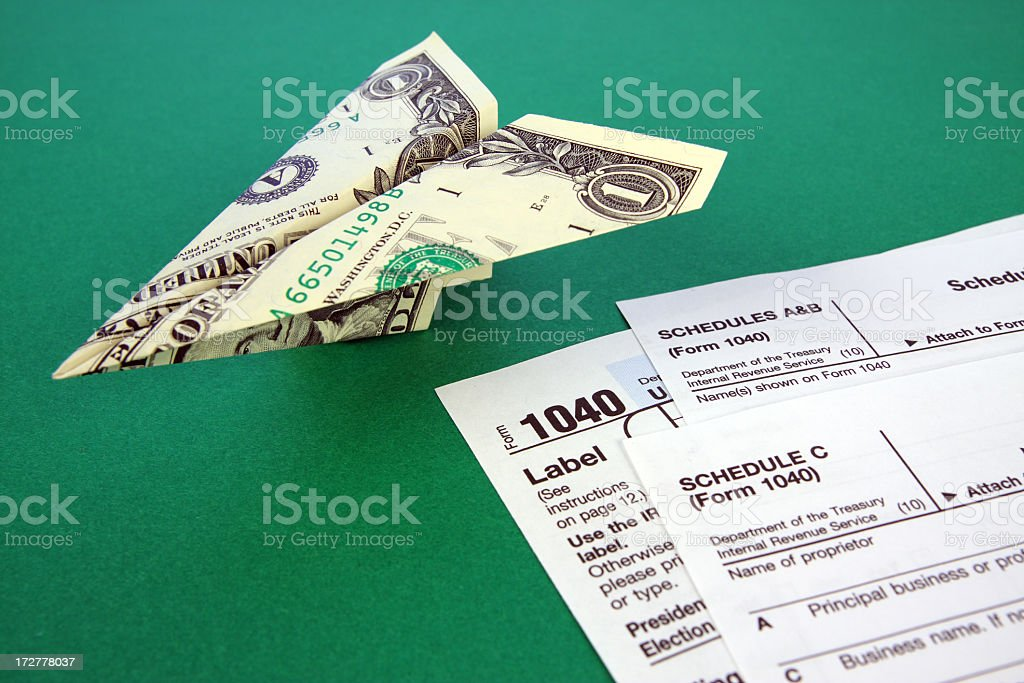 Dollar-Bill Paper Airplane Next to Tax Forms on Green Background stock photo