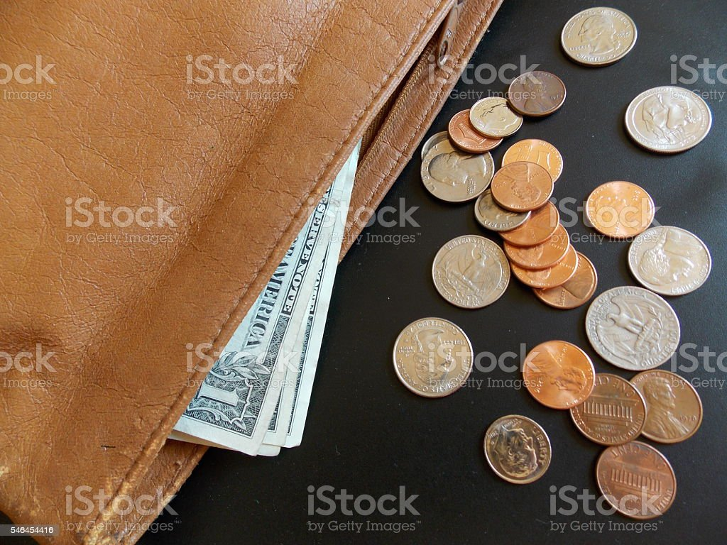 US Dollars and Coins Spilling Out of a Purse stock photo