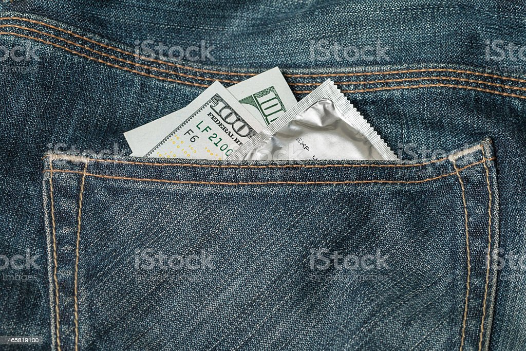 US dollars and condom in the jeans pocket stock photo