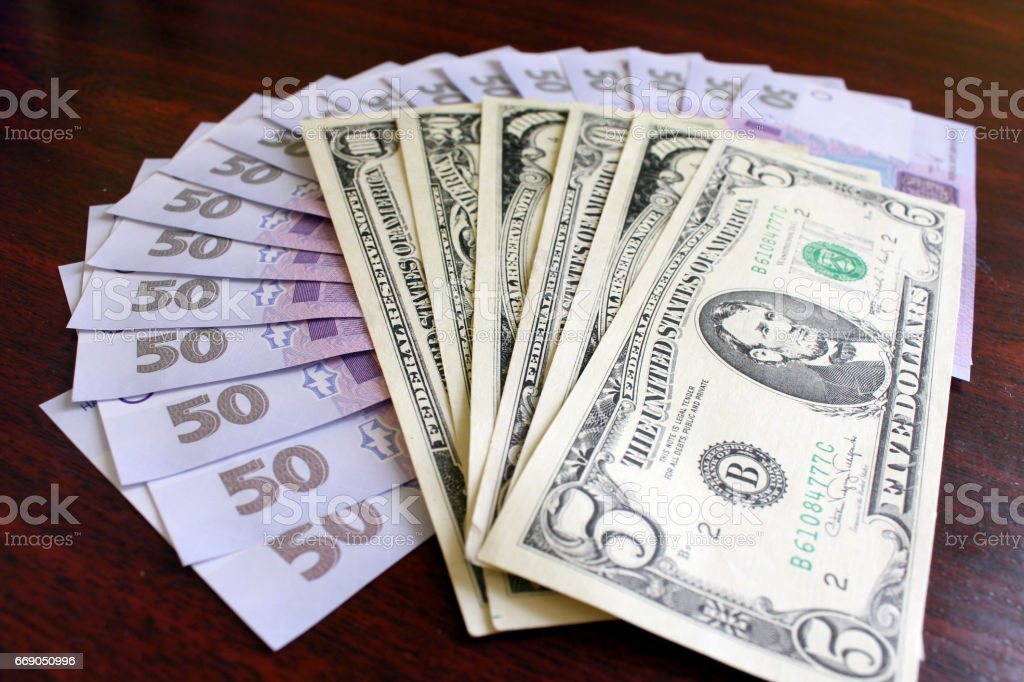 dollars and grivnas banknotes on the dark stock photo