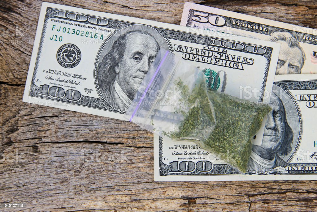 Dollars and marijuana in packet on wooden background stock photo