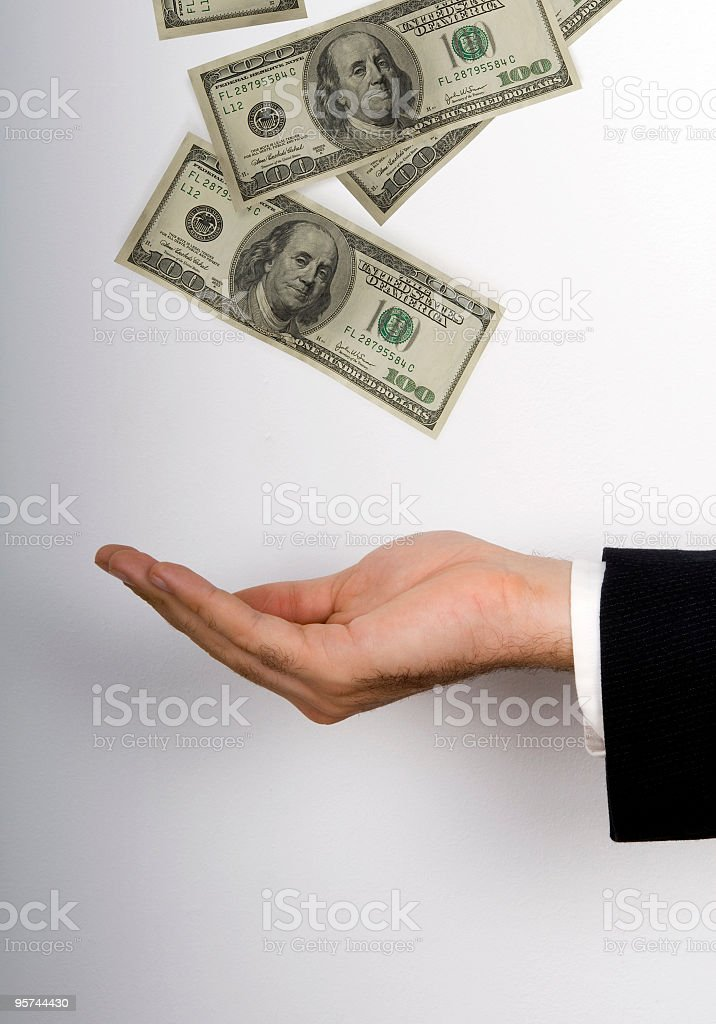 US Dollars floating in air above businessman's hand stock photo