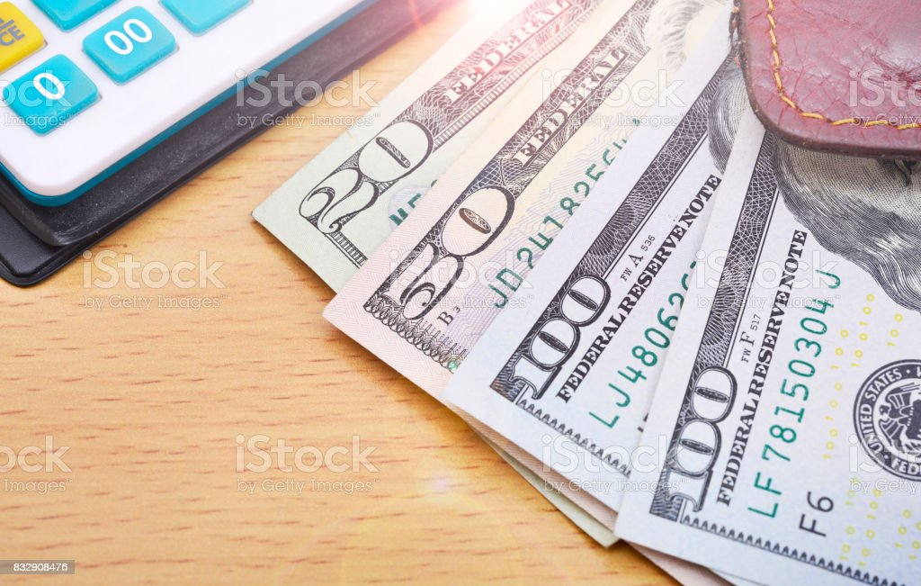 Dollars in wallet and calculator stock photo