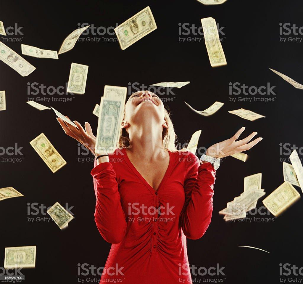 Dollars rain down on pretty blonde who smiles ecstatically stock photo