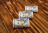 US Dollars rolled into a roll and tied with thread