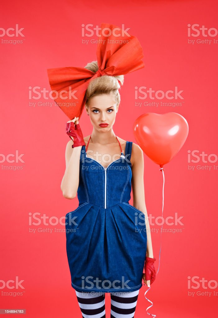 Doll-like woman with red heart shaped balloon stock photo