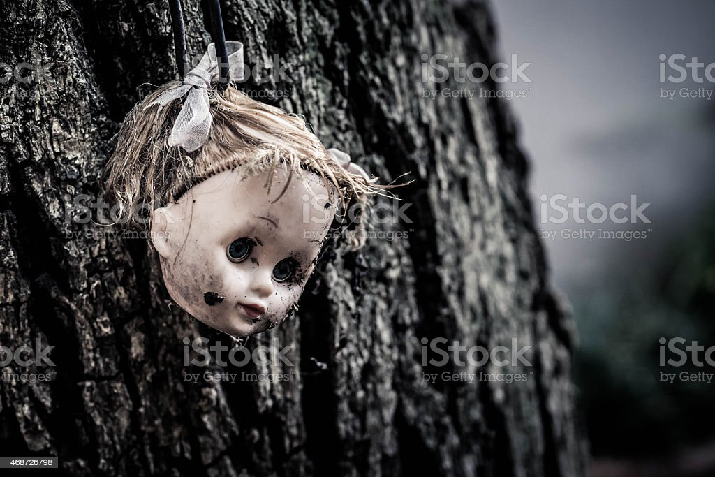 Doll's Head Hanging From Tree Landscape stock photo