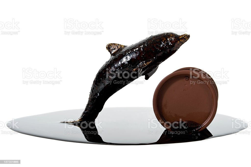 Dolphin jumping a drum leaking crude oil stock photo