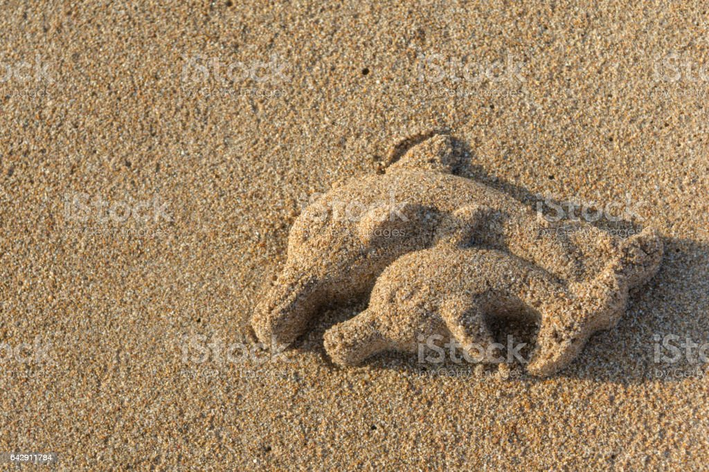 Dolphin sculpture on the sand stock photo