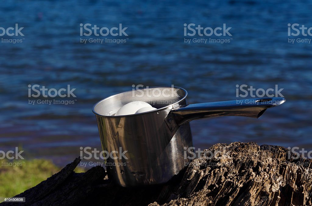 Domestic boiled eggs cooling on a lake shore in a stock photo