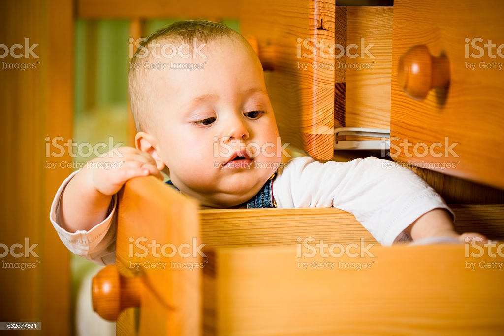 Domestic chores - baby opens drawer stock photo