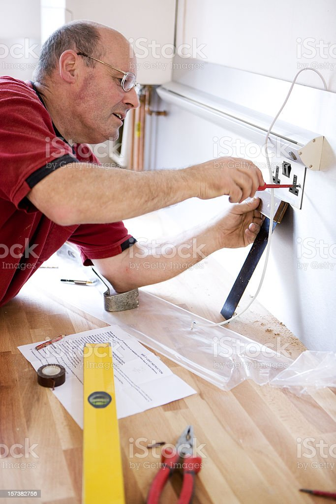 Domestic kitchen fitter installing an electrical wall plug socket royalty-free stock photo