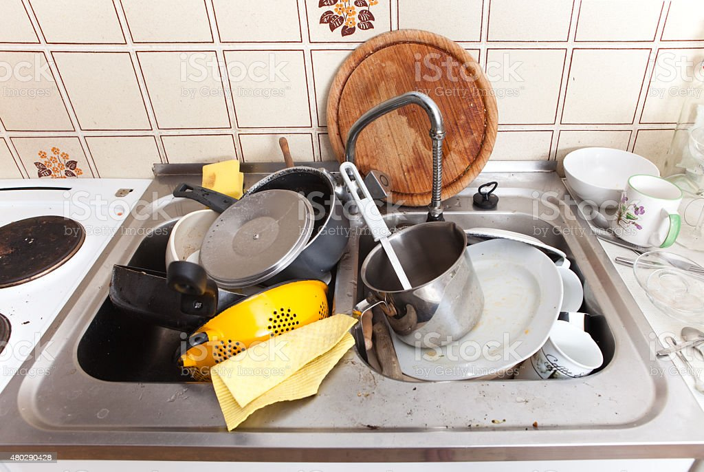 domestic kitchen with dirty crockery and cutlery in messy sink stock photo