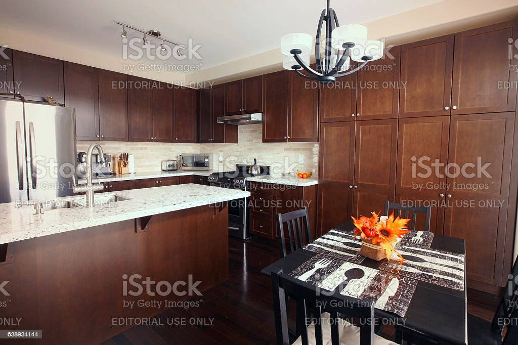 Domestic kitchen with quartz countertops and brown cabinetry stock photo