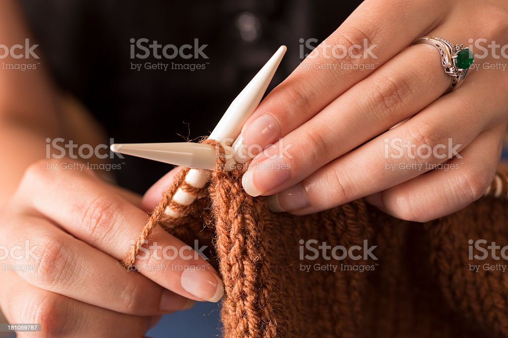 Domestic Life:  Young adult woman knitting.  Back to basics.. royalty-free stock photo