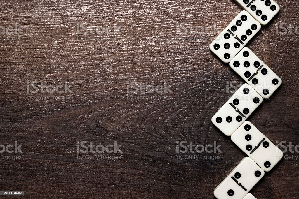 domino pieces forming zigzag over wooden table stock photo