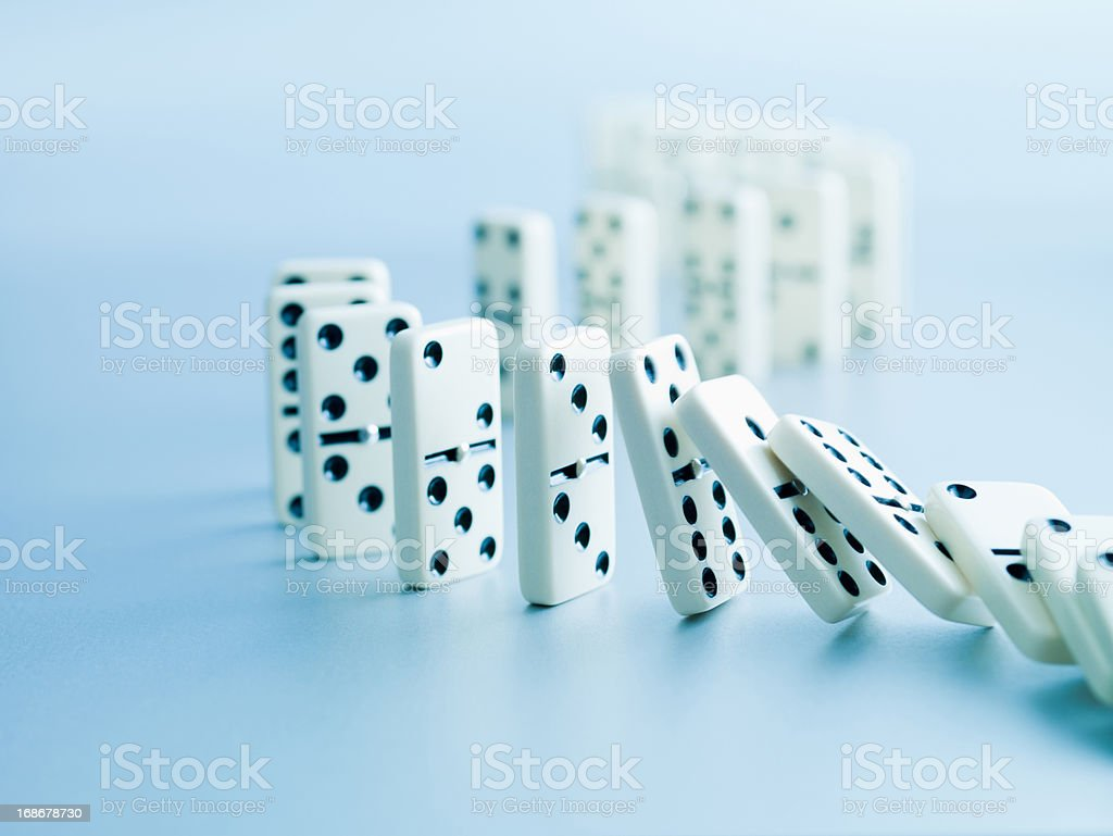 Dominoes falling in a row stock photo