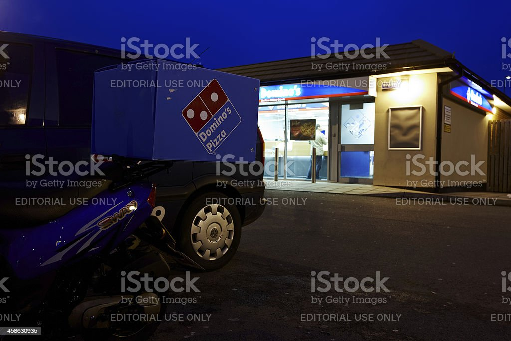 Dominos pizza delivery vehicles and restaurant at night royalty-free stock photo