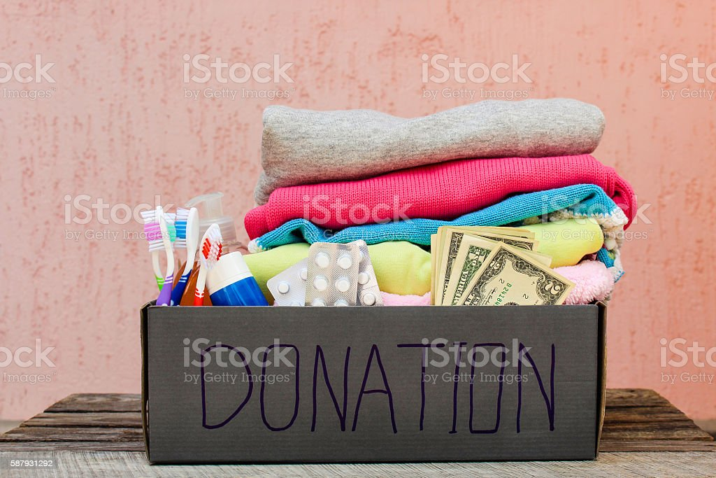 Donation box with clothes, living essentials and money stock photo